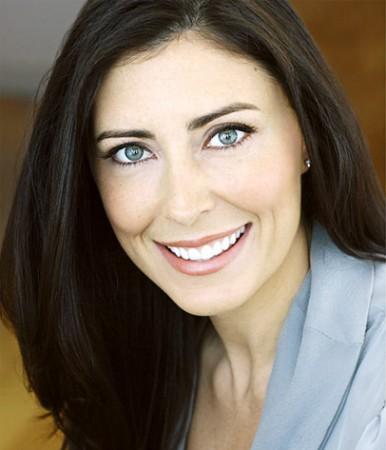 Headshot of Aimée Steele smiling wearing a light blue jacket.